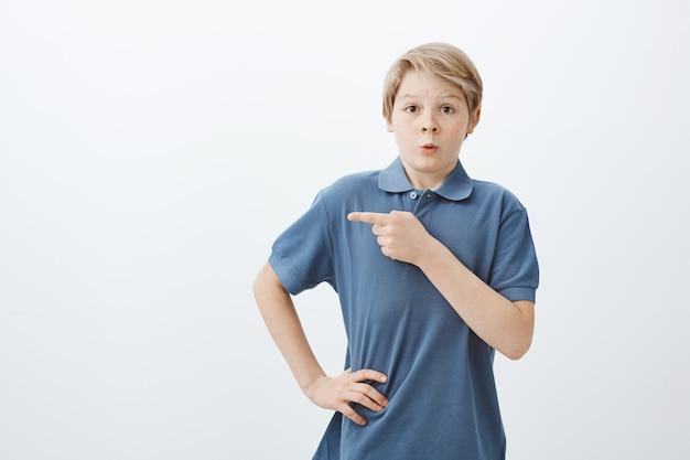 Foto interna de um menino loiro encantador e nervoso com uma camiseta azul, segurando a mão no quadril e apontando para a esquerda com o dedo indicador