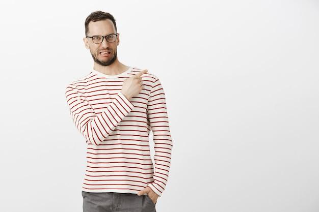 Foto interna de um modelo masculino engraçado desgostoso e descontente com cerdas em óculos pretos