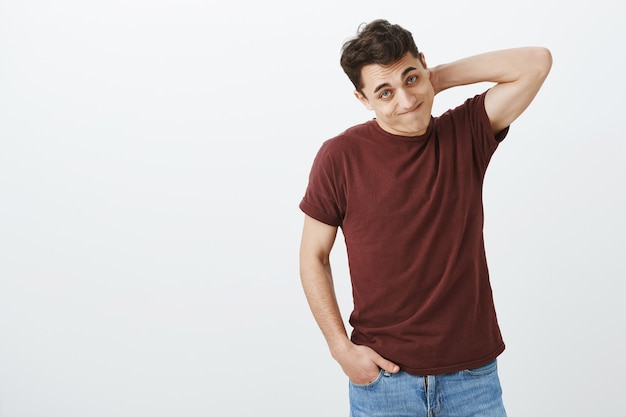 Foto interna de um modelo masculino europeu envergonhado e culpado em uma camiseta vermelha casual