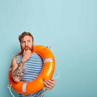 Foto interna de um nadador inexperiente e pensativo segurando o queixo, focado para cima
