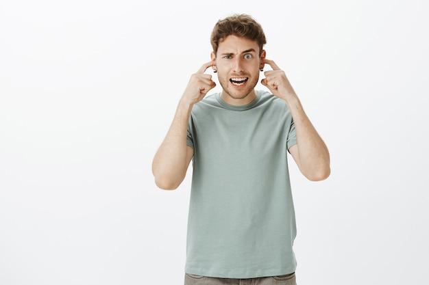 Foto interna de um namorado caucasiano engraçado em uma camiseta casual, fazendo caretas, cobrindo a audição com o dedo indicador nas orelhas