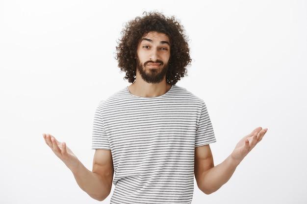 Foto interna de um namorado hispânico confuso e sem noção com penteado afro e barba masculina, levantando as palmas das mãos e erguendo as sobrancelhas