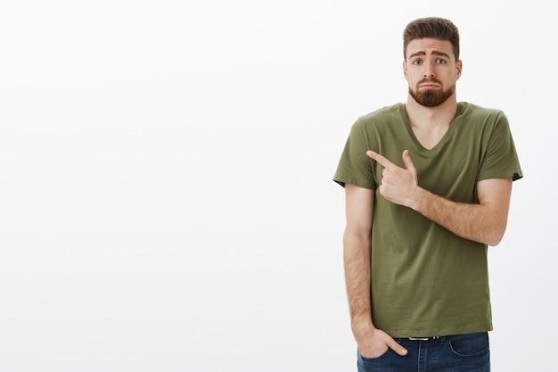 Foto interna de um namorado triste, inocente e fofo, triste, com barba e olhos azuis segurando a mão no bolso, fazendo beicinho e franzindo a testa, ofendido e desapontado apontando com pesar para o canto superior esquerdo