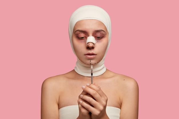 Foto interna de um paciente intrigado olhando para seringa com vacina, gesso no nariz após remodelagem e melhora