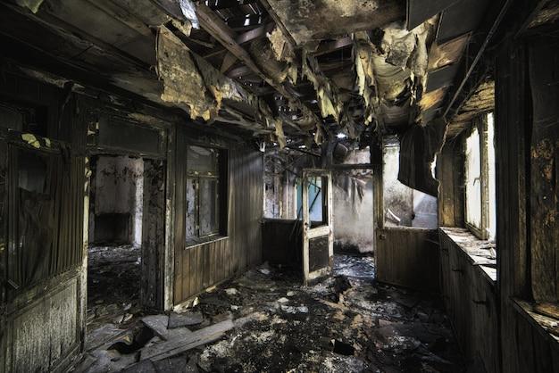 Foto interna de um prédio abandonado destruído com paredes queimadas e portas gastas