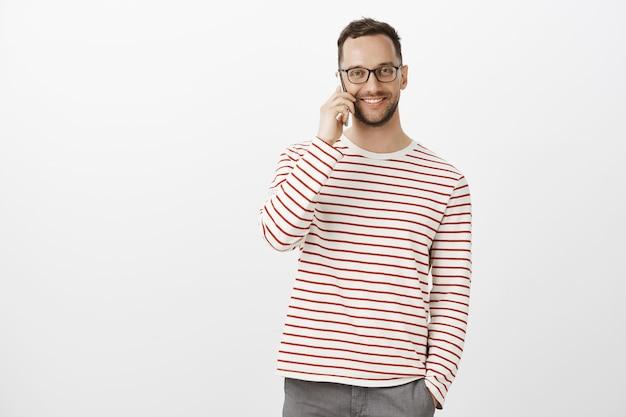 Foto interna de um trabalhador de escritório adulto amigável e satisfeito com uma camisola listrada e óculos, falando casualmente no smartphone
