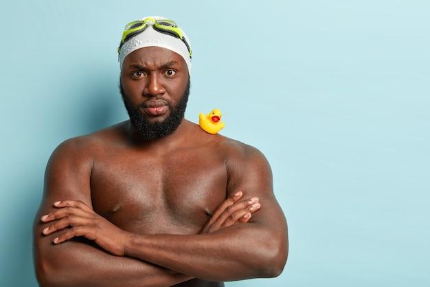 Foto interna de um treinador de natação rigoroso e sério com braços musculosos cruzados sobre o peito, zangado com o trainee, pele morena saudável, usa óculos de proteção e chapéu de natação, pequeno patinho amarelo de borracha no ombro forte