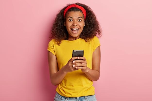 Foto interna de uma adolescente divertida com cabelo encaracolado posando em uma camiseta amarela