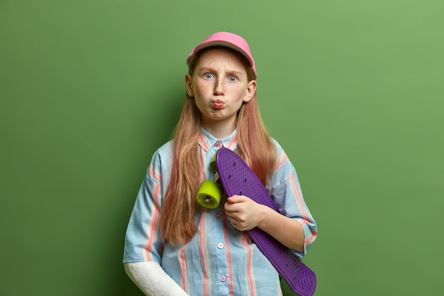 Foto interna de uma adolescente engraçada mantém os lábios arredondados, segura o skate, vestida com uma camisa listrada e boné, quebrou o braço após uma queda acidental durante o skate, faz uma careta. filhos, estilo de vida