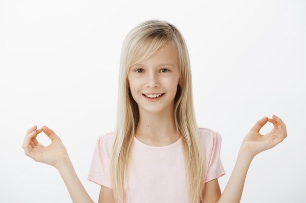 Foto interna de uma adorável criança curiosa com cabelo loiro, estendendo as mãos em gestos zen e sorrindo com expressão satisfeita, meditando ou praticando ioga, em pé sobre uma parede cinza calma