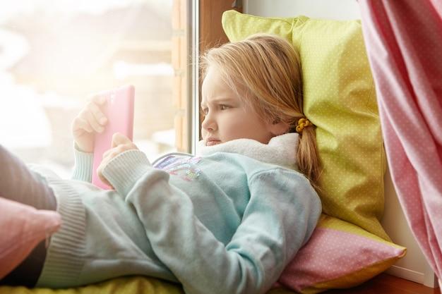 Foto interna de uma adorável criança europeia com uma aparência séria e concentrada enquanto usa o telefone