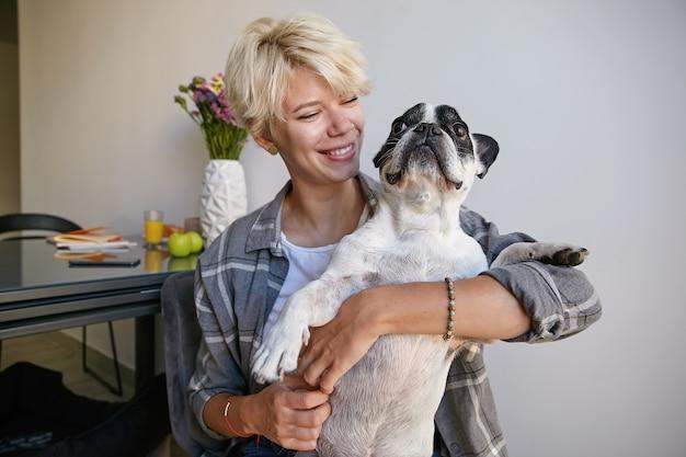 Foto interna de uma adorável jovem loira posando no interior da casa com seu lindo buldogue francês preto e branco, abraçando o cachorro com um olhar amoroso e terno