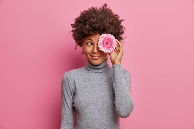 Foto interna de uma adorável jovem romântica segurando uma flor sobre os olhos, com um sorriso gentil, vestindo uma blusa de gola alta cinza casual