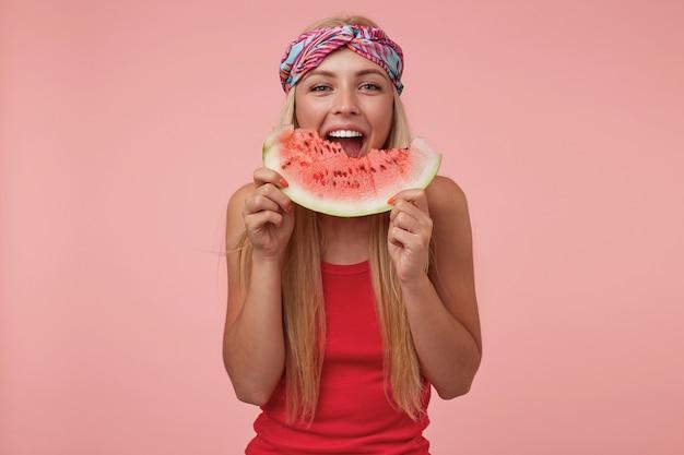 Foto interna de uma alegre linda mulher com fita na cabeça e longos cabelos loiros posando, comendo melancia e de bom humor