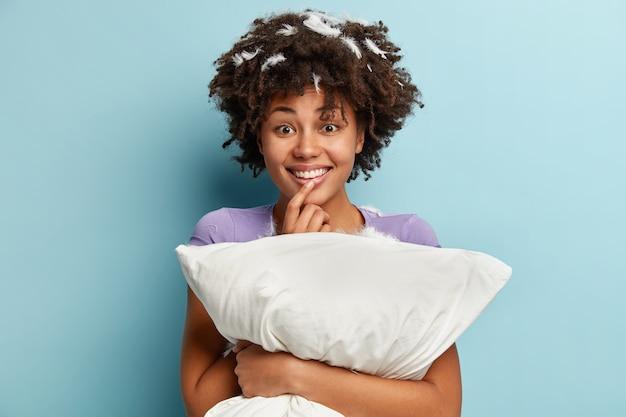 Foto interna de uma alegre mulher de pele escura segurando um travesseiro branco macio, dorme bem à noite, desfruta de descanso, conforto e lazer, tem uma expressão alegre, fica de pé sobre uma parede azul. pessoas, despertando o conceito
