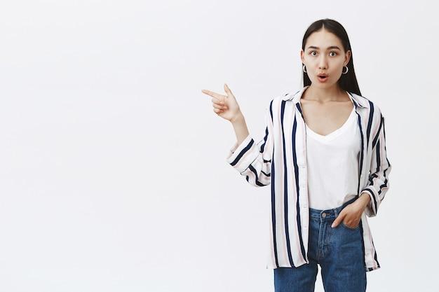 Foto interna de uma aluna encantadora impressionada e surpresa em uma blusa listrada estilosa, segurando a mão no bolso e apontando para a esquerda com o dedo indicador, ofegando de espanto, em pé sobre uma parede cinza