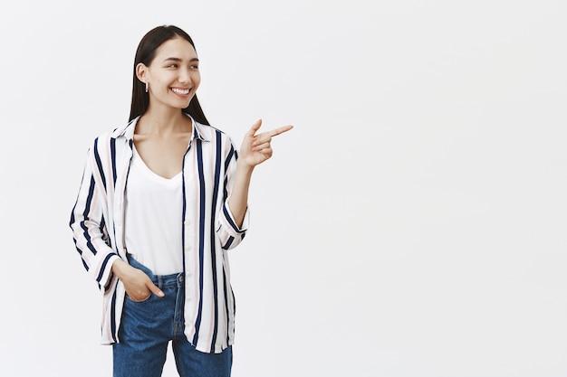 Foto interna de uma atraente e bela funcionária europeia apontando e olhando para a direita com um largo sorriso satisfeito, segurando a mão no bolso, em pose confiante, em pé sobre uma parede cinza