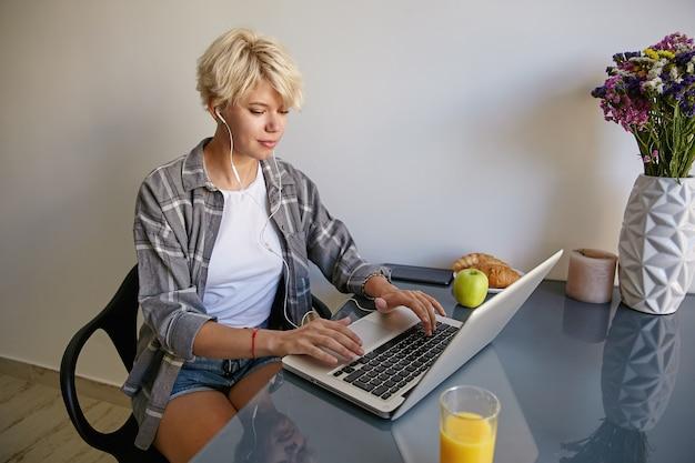 Foto interna de uma atraente jovem loira sentada na cadeira com fones de ouvido, usando um laptop, trabalhando online em casa e vestindo roupas casuais