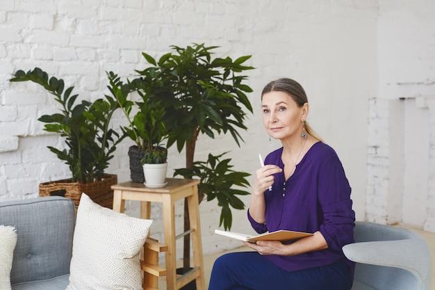 Foto interna de uma atraente treinadora de negócios europeia de meia-idade, pensativa, sentada em uma sala espaçosa e iluminada, rodeada de móveis modernos e vasos de plantas, verificando a agenda em seu diário