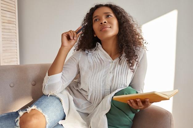 Foto interna de uma bela jovem afro-americana de blusa e jeans rasgado, com expressão facial pensativa, olhando para cima, coçando a cabeça com uma caneta, fazendo anotações no caderno, desenvolvendo plano de negócios