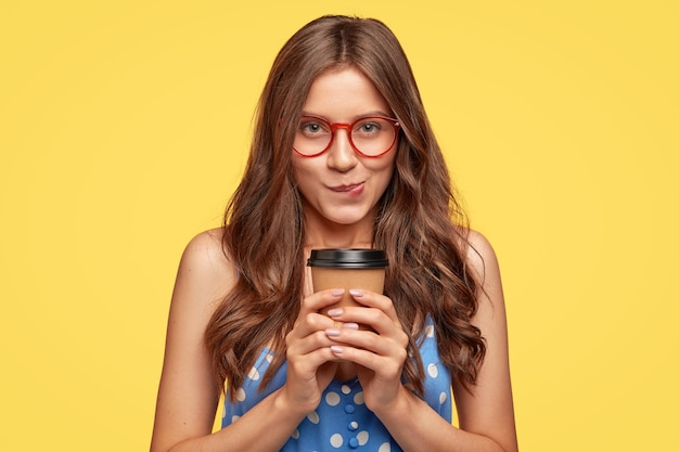 Foto interna de uma bela jovem com óculos posando contra a parede amarela