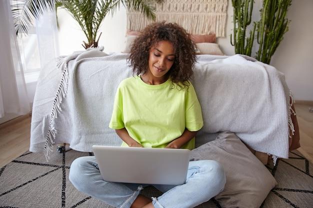 Foto interna de uma bela jovem de pele escura com cabelo castanho encaracolado, segurando o laptop nas pernas e olhando para a tela, usando roupas casuais