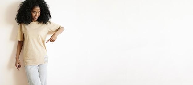 Foto interna de uma bela jovem de pele escura com sorriso fofo e penteado afro, olhando para sua camiseta casual grande e apontando o dedo para ela