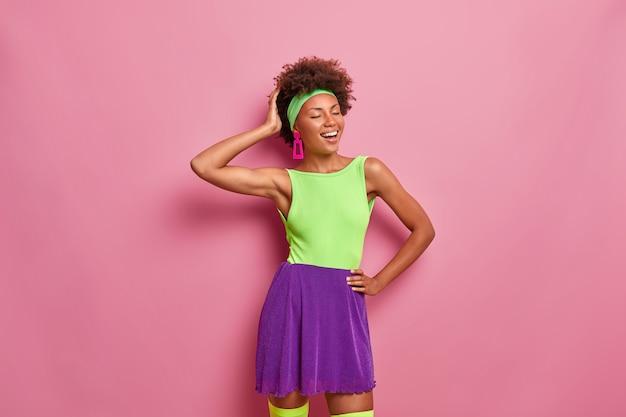 Foto interna de uma bela mulher étnica de cabelos cacheados com olhos fechados, sorrindo sinceramente, vestindo camiseta e saia coloridas