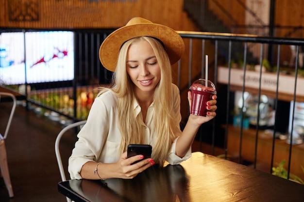 Foto interna de uma bela mulher loira de cabelos compridos, sentada à mesa no café da cidade e segurando o smoothie na mão levantada, segurando o telefone celular e olhando positivamente na tela