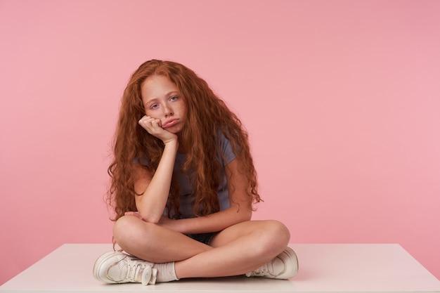 Foto interna de uma criança com cabelo encaracolado de raposa, inclinando a cabeça na mão levantada enquanto está sentada com as pernas cruzadas sobre um fundo rosa em roupas casuais, olhando para a câmera com o rosto entediado