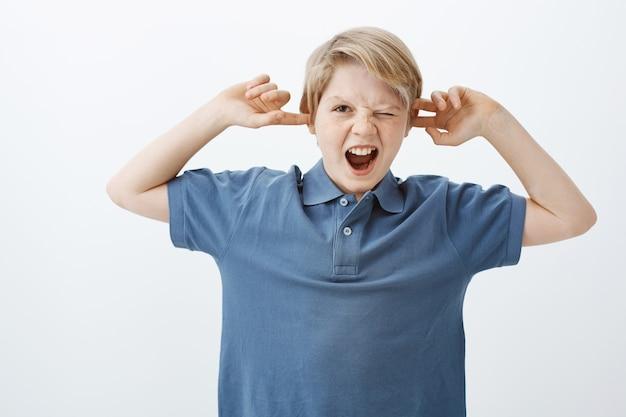 Foto interna de uma criança europeia infeliz e irritada em uma camiseta azul, gritando ou gritando, cobrindo as orelhas com o dedo indicador, espiando com um olho