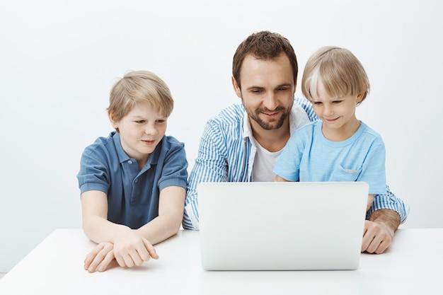 Foto interna de uma criança loira feliz positiva com pai e irmão sentados à mesa, olhando para a tela do laptop e sorrindo amplamente
