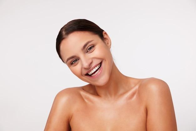 Foto interna de uma encantadora jovem feliz de cabelos escuros com maquiagem natural, parecendo alegre e rindo alegremente, em pé com ombros nus