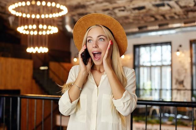 Foto interna de uma encantadora jovem loira posando sobre o interior do café com uma cara surpresa, olhando para o lado com uma ampla motuh aberta e a palma da mão na bochecha, ouvindo notícias inesperadas em seu telefone