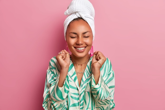 Foto interna de uma feliz mulher de pele escura em pé com os olhos fechados, cerrando os punhos, alegra-se com as boas notícias, vestida com manto doméstico, toalha de banho embrulhada. dona de casa passa fim de semana em casa. atmosfera aconchegante