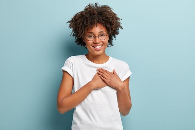 Foto interna de uma feliz senhora de pele escura xingando ou prometendo algo, segurando as mãos no peito, dizendo a verdade, sendo honesta, olhando para a câmera