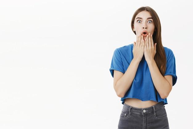 Foto interna de uma fofa morena europeia divertida, chocada e muda, usando uma camiseta azul, ofegando de emoção, segurando as palmas das mãos no queixo, divertida e surpresa, olhando espantada contra a parede cinza