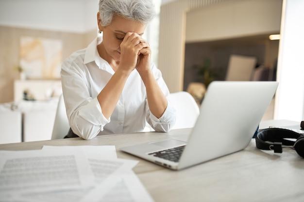 Foto interna de uma frustrada e infeliz empresária de meia-idade gerenciando papéis enquanto está sentada na mesa do escritório em frente a um laptop aberto, olhando para baixo com as mãos no rosto