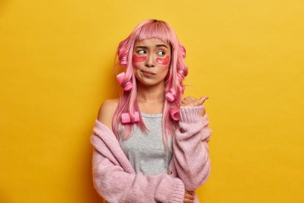 Foto interna de uma garota asiática confusa com longos cabelos rosa, faz penteado encaracolado com rolos, aponta para o espaço da cópia e tem uma expressão desagradada