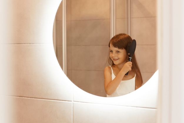 Foto interna de uma garota de cabelos escuros penteando o cabelo no banheiro, fazendo procedimentos de beleza matinais na frente do espelho, sorrindo feliz, vestindo roupas de estilo casual para casa.