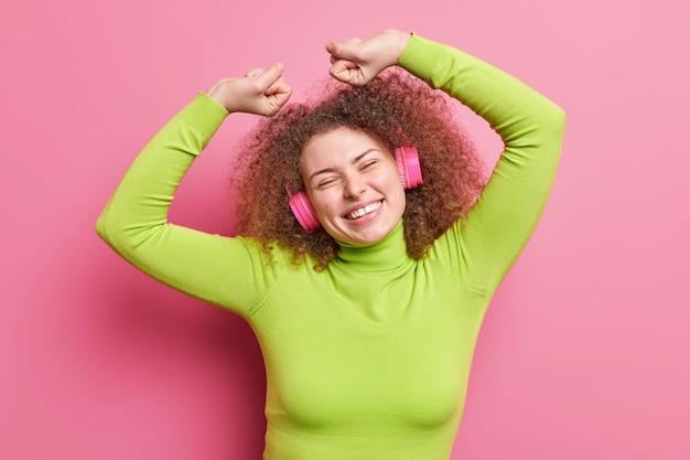 Foto interna de uma garota europeia despreocupada com cabelo encaracolado levanta os braços e fecha os punhos celebra o sucesso vestida com macacões casuais com ritmo de música usando fones de ouvido sem fio poses sobre uma parede rosada