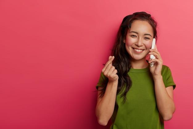 Foto interna de uma garota feminina bonita com um sorriso largo faz um sinal de coreano, expressa afeto enquanto conversa com o namorado ou noivo via celular