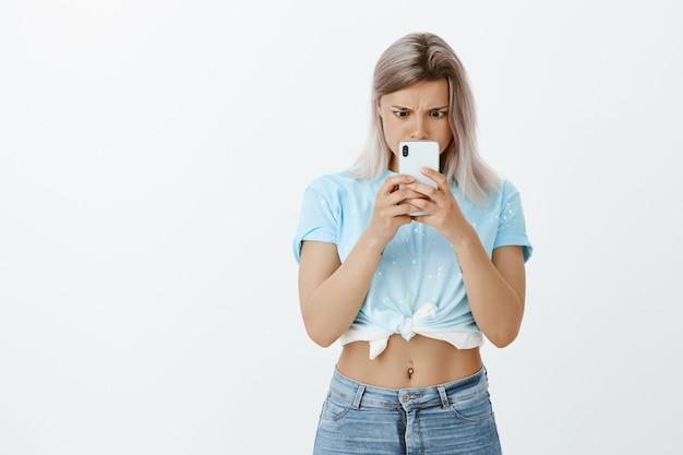 Foto interna de uma garota loira em choque posando no estúdio com seu telefone