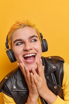 Foto interna de uma garota punk cheia de energia ouve música, rindo e brinca alegremente tem uma aparência única, um estilo extraordinário estando de bom humor entretém durante o tempo livre