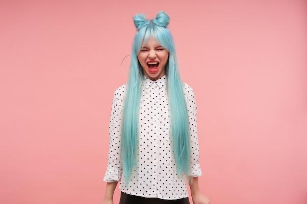 Foto interna de uma jovem adorável mulher com cabelo azul anime, mantendo os olhos fechados enquanto grita alto, usando um penteado coque em pé com as mãos para baixo