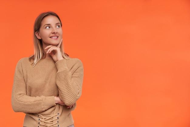 Foto interna de uma jovem adorável mulher de cabelos brancos com penteado casual mordendo o lábio inferior enquanto olha para o lado positivamente e apoiando o queixo na mão levantada, isolado sobre uma parede laranja