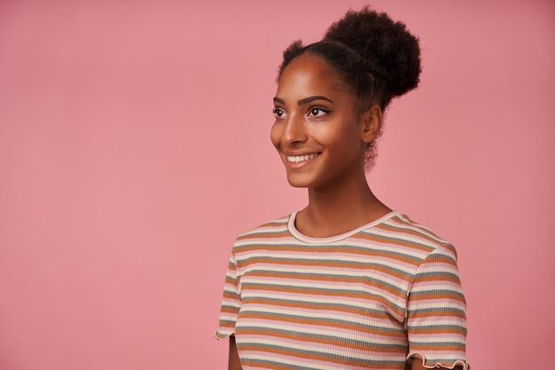 Foto interna de uma jovem adorável mulher de olhos castanhos encaracolados olhando positivamente de lado com um sorriso encantador enquanto posava sobre uma parede rosa com as mãos para baixo