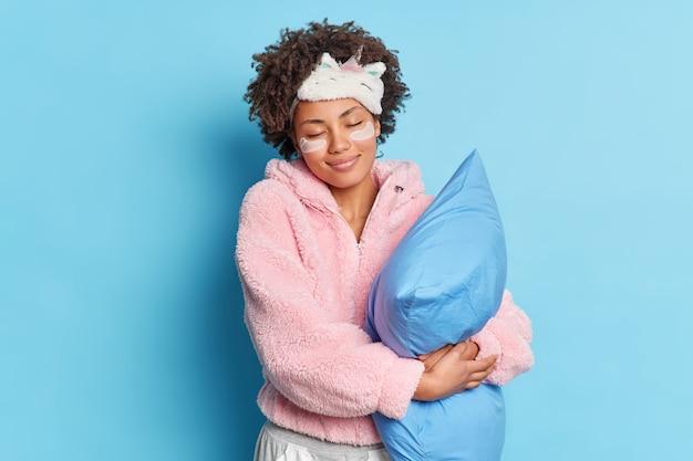 Foto interna de uma jovem afro-americana positiva posando com sorrisos de olhos fechados e um travesseiro macio