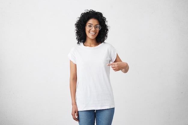 Foto interna de uma jovem afro-americana sorridente e alegre com cabelo encaracolado apontando o dedo indicador