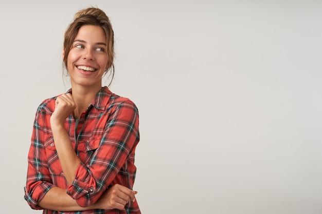 Foto interna de uma jovem alegre mulher de cabelos castanhos vestida com uma camisa quadriculada, rindo alegremente enquanto olha para o lado, posando sobre um fundo branco com a mão levantada